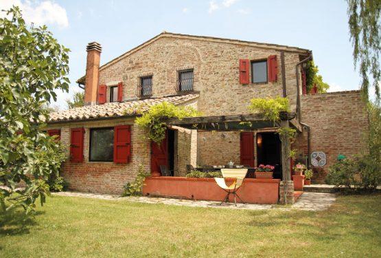 Il casale dalle finestre rosse tra le verdi colline della Toscana